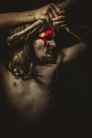 Wild warrior with metal sword and war paintings on the face, long hair
