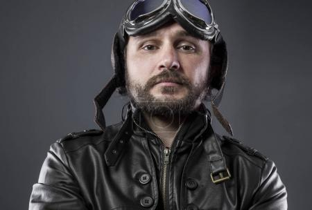 recreation of the Second World War, old airplane pilot with brown leather jacket, cap of avidor and large glasses