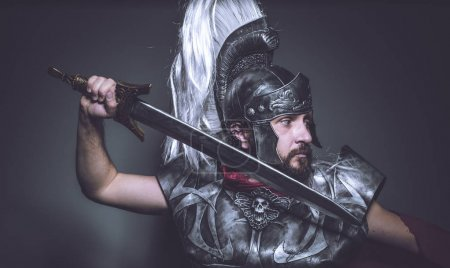 Violence Roman gladiator, wrestler and warrior of Rome with helmet and red cloak, carries an iron sword, beard and long hair.