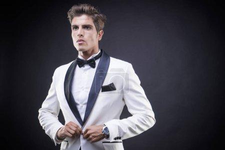 Stylish Luxury, elegant man in a white suit tuxedo with bow tie around his neck
