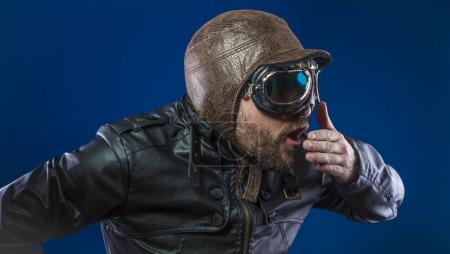 Accident, pilot of the 20s with sunglasses and vintage aviator helmet. Wears leather jacket, beard and expressive faces