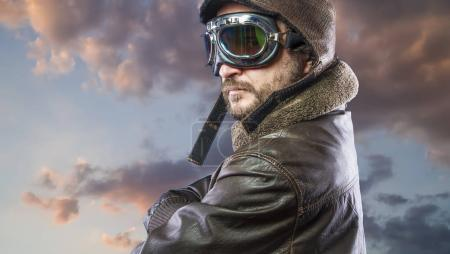 Proud, pilot of the 20s with sunglasses and vintage aviator helmet. Wears leather jacket, beard and expressive faces