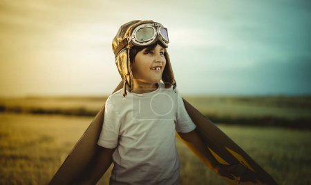 Freedom, Happy child playing with toy wings against summer sky background. Retro vintage toned. Travel and adventure concept