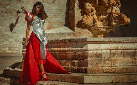 Foto de Medieval, hermosa mujer morena con corsé de oro y cobre en poses de diosa y guerrera. concepto de fantasía e imaginación - Imagen libre de derechos