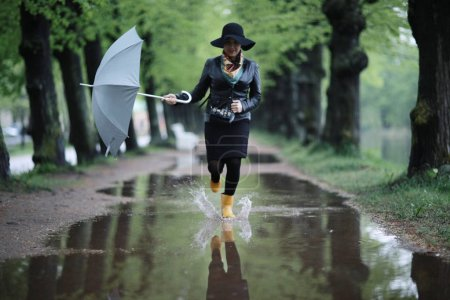 Photo for Woman running in street with puddles holding umbrella - Royalty Free Image