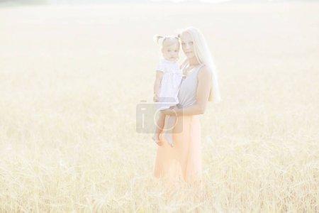 mother hugging daughter in field