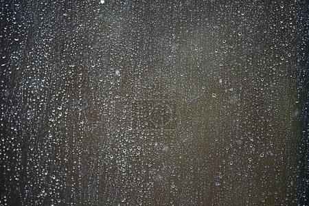 Raindrops flowing  down the glass