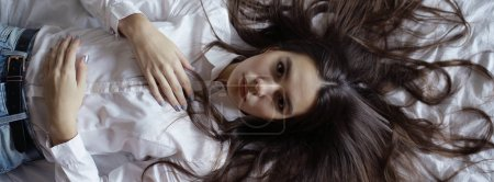 teenage girl with long hair in bed
