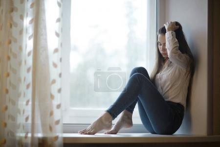 sad teenage girl sitting on windowsill