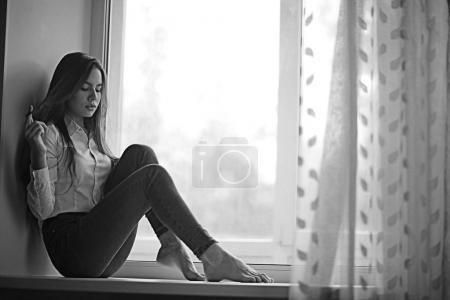 teenage girl sitting on windowsill