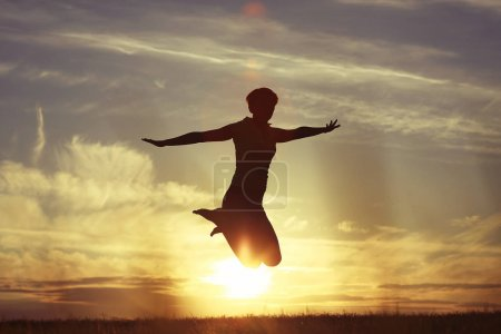 woman jumping against sunset sky