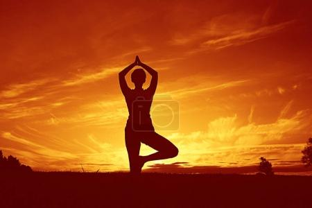 woman doing yoga against sunset sky