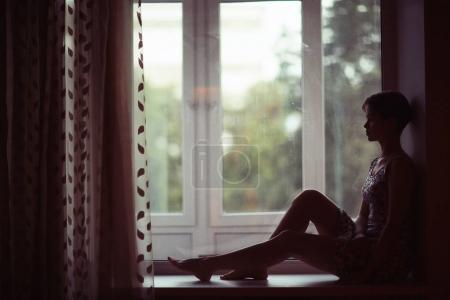 woman sitting on windowsill