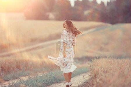 Photo pour Fille court sur un champ d'été dans un blé habillé, soleil couchant jour ensoleillé concept liberté bonheur - image libre de droit
