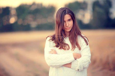 Photo pour Jeune brune en été aux cheveux longs dans un champ, heureuse santé beauté posant au coucher du soleil - image libre de droit