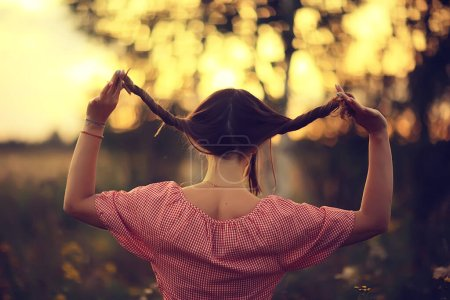 Photo for Pigtails view from the back, young adult girl rustic style happiness freedom summer, no face - Royalty Free Image
