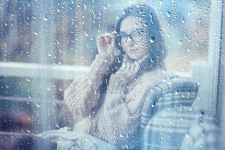 Photo pour Café d'automne un jour de pluie, fille derrière un verre avec une tasse de café chaud - image libre de droit