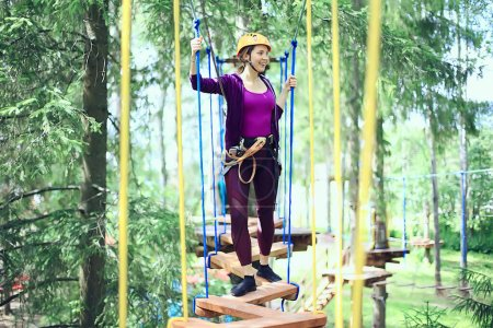 Photo for Extreme vacation, girl in a yellow helmet rope park active holidays in the forest - Royalty Free Image