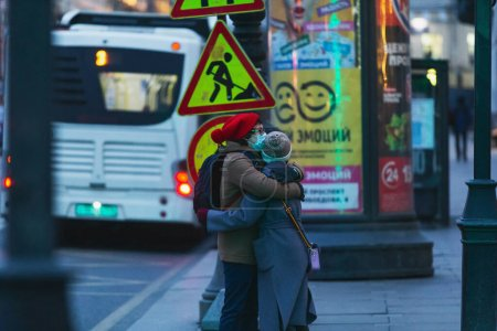 Photo for Saint-petersburg, Russia - 31 March 2020: Man and woman in masks hugging at the pedestrian crossing. Empty evening city on 1st day of self isolation in the dusk. - Royalty Free Image