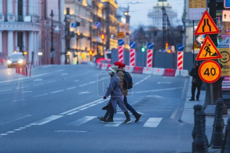 Photo for Saint-petersburg, Russia - 31 March 2020: Man and woman in masks each other hands while cross the road at a pedestrian crosswalk. Empty evening city on 1st day of self isolation in the dusk. - Royalty Free Image