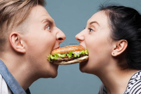 Photo for Man and woman eating a burger - Royalty Free Image
