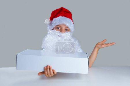 Photo pour Le petit Père Noël leva la main gauche, la paume vers le haut, boîte blanche enveloppée à droite. Il est assis à une table blanche. Il regarde dans la caméra. Fond gris. Gros plan . - image libre de droit