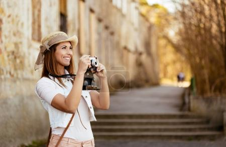Photo for Beautiful young tourist holding a camera while taking pictures outside in the nature. - Royalty Free Image