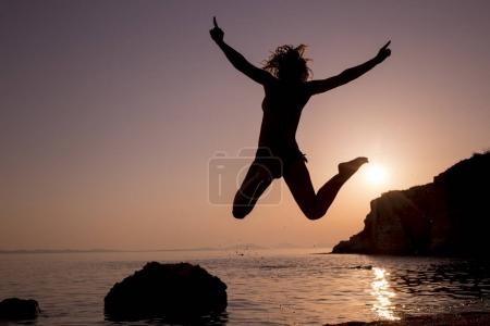 Happy young woman jumping on the beach at sunset