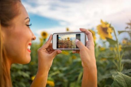 Beautiful young woman taking a picture of a sunflower