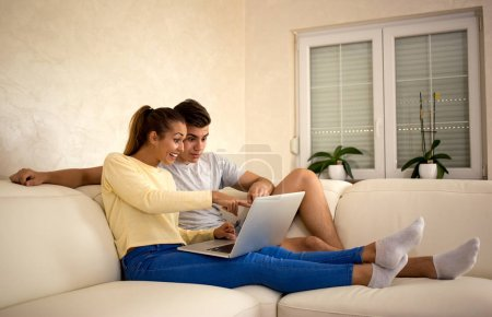 young couple sitting on the couch while looking at a laptop