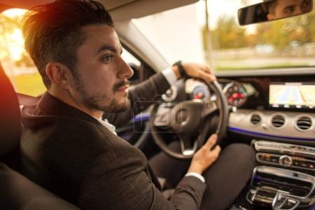 Handsome businessman driving car