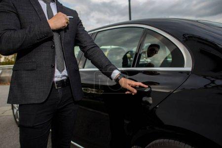 Photo pour Homme ouvrant une voiture noire limousines porte - image libre de droit