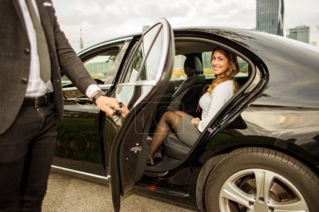 Handsome man holding car door for beautiful businesswoman