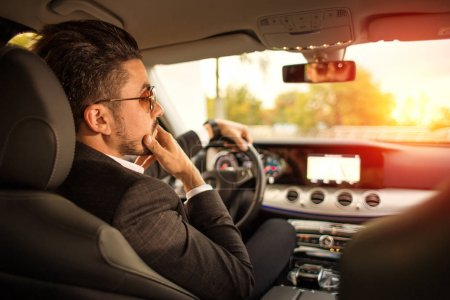 Handsome businessman driving car