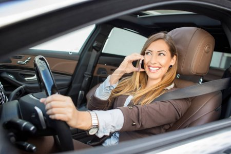 Beautiful business woman talking on the phone while driving
