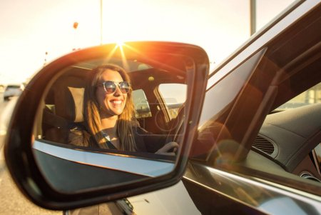 Photo for Beautiful businesswoman in rear view mirror with sunglasses smiling - Royalty Free Image