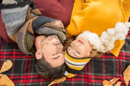 Happy couple lying on picknick blanket in autumn