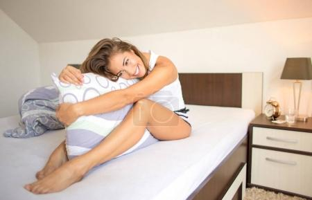 Beautiful woman sitting in bed with pillow