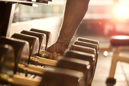 Closeup of mans hand grabbing a dumbbell weight
