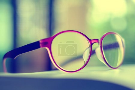 Eyeglasses placed on the book, extremely DOF with vintage retro color tone