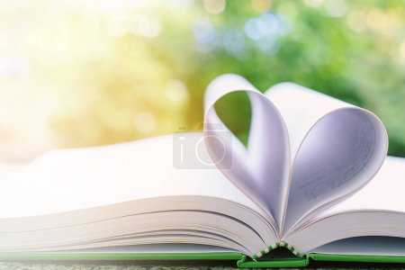 Opened book with heart shaped page on blurred natural green back