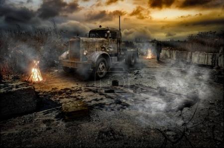 Foto de Escena apocalíptica. Carretera rota abandonada, un hombre distante, incendios ardientes, un camión tractor, humo y caos alrededor . - Imagen libre de derechos