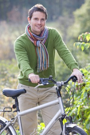 Smiling man standing outdoors with bicycle