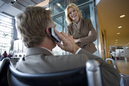 Businessman wearing casual suit talking on cell phone near female colleague