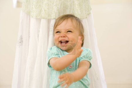 Toddler boy (15-18 months) laughing by mother, close-up
