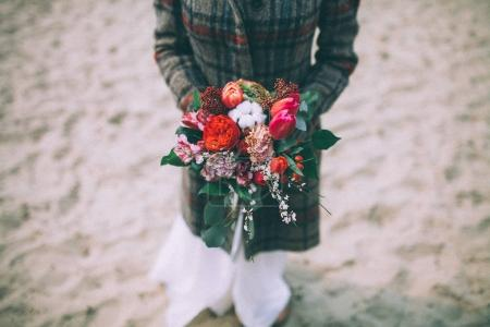 Bride with bouquet in dress and coat