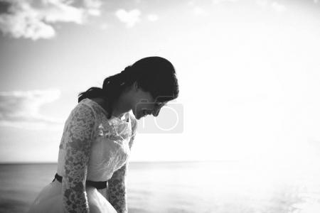 Bride in white dress laughing and looking down