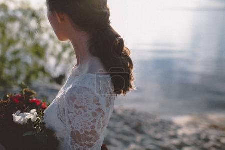 Cropped view of woman in wedding dress on shore