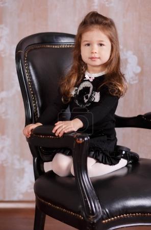 Jeune fille brune poupée dame élégant habillé comme un patron en chemise officielle blanche jupe noire posant assis en studio sur une chaise en cuir noir avec des lèvres pâles et des joues roses .