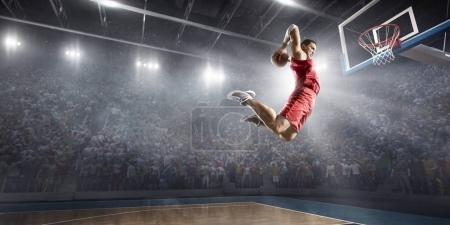 Photo pour Joueur de basket fait un slam dunk sur une arène de basket-ball. Il porte des vêtements sans marque. - image libre de droit